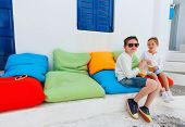 pic of brother sister  - Two cute kids brother and sister drinking fresh smoothies on a colorful pillows at outdoor cafe on summer day - JPG