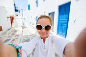 picture of greek-island  - Little tourist girl taking selfie with mobile phone on a street of traditional greek village on Mykonos island - JPG