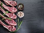 foto of lamb chops  - Raw lamb chops with garlic and herbs on the old wooden table - JPG