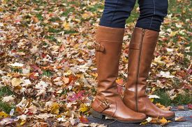 foto of jeans skirt  - Woman wearing brown boot  and standing on foliage - JPG