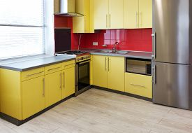 picture of hoods  - yellow kitchen with cupboards with hinged doors topped with a grey worktops and fitted with appliances including refrigerator microwave oven extractor hood a wall with a red tile and floor with soft sand grey laminate - JPG
