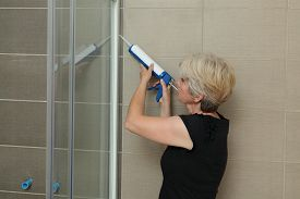 foto of cartridge  - Woman using silicone cartridge for fixing aluminum batten of shower cabin - JPG