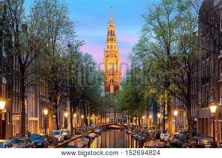 poster of Amsterdam Zuiderkerk church tower at the end of a canal in the city of Amsterdam Netherlands at night . Amsterdam is the capital and most populous city of Netherlands