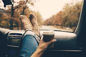 Woman feet in warm socks on car dashboard. Drinking take away coffee on road. Fall trip. Rain drops  poster