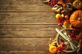 Autumn background from fallen leaves and fruits with vintage place setting on old wooden table. Than poster