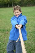 stock photo of tug-of-war  - A smiling boy invites to a good game of tug - JPG