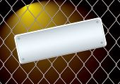 Wire fence with a metal blank sign attached at night with bright light