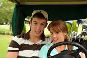 Cute young couple in a golf cart