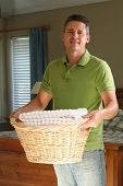 Attractive man holding a basket of clean laundry.