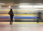 Lone woman watching subway speed by