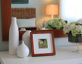 Picture frame and flowers on a dresser in a contemporary bedroom. (Picture in frame is mine.)