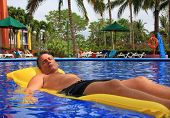 Man relaxing on a floating mattress in a swimming pool.