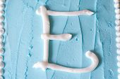 White Icing Letter E On A Blue Cake (series Spells Love)