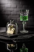 Close-up Shot Of Glass Of Absinthe With Slice Of Cheese On Dark Brick Wall Background poster
