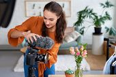 Young female vlogger adjusting her video equipment for her daily vlog video diary poster