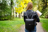 Rear View Of Young Adult High School Or College Student Girl Walking In The Park On Her Way To Class poster