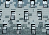 A wall with a lot of square glass windows on the building. The rhythm of the windows. poster