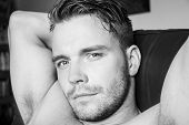 Hunky Muscular, Sexy Shirtless Man With Muscules And Pecs Sitting On Sofa, Looking At Camera poster