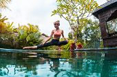 Young woman performs yoga exersices in the tropical garden near the pool poster