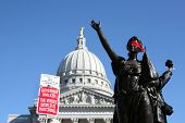 MADISON,WI - FEB 19: Signs are lifted in front of Wisconsin's Capitol protesting Gov Scott Walker on
