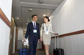 business trip and people concept - man and woman with travel bags and conference badges at hotel cor poster