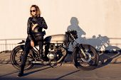 Sexy biker young woman in black trendy leather jacket sit on vintage custom made caferacer motorcycl poster