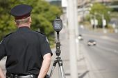 stock photo of cap gun  - A North American policeman waits to catch speeding drivers with a radar gun - JPG