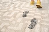 Person In Dirty Shoes Leaving Muddy Footprints On Carpet poster
