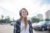 Street Portrait Of A Girl In Casual Clothes Standing In The Parking Lot And Listening To Music The H poster