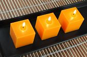 three orange candles in black dish on bamboo