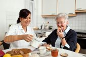 foto of nursing  - a geriatric nurse helps elderly woman at breakfast - JPG