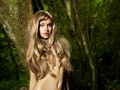 Portrait of a nude elegant lady in a green rainforest