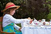 Beautiful Little Girl Having A Garden Tea Party Alone