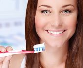 Closeup portrait of beautiful young woman brushing her teeth in bathroom, perfect smile, dental care