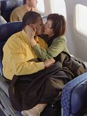 Mature couple kissing and cuddling on airplane