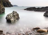 Long exposure flowing tide over and around rocks