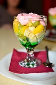 stock photo of souse  - Glass with fruits dessert with mint souse and weep cream.