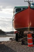 stock photo of lobster boat  - A lobster fishing boat sits on blocks waiting for the season to open in Eastern Canada - JPG