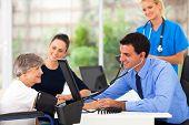 friendly medical doctor taking senior woman's blood pressure