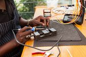 senior african electrician using soldering iron repair a push button