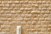 Texture of the wall built of rough yellow stone blocks