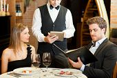 stock photo of fiance  - Couple ordering meal at restaurant - JPG