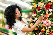 Beautiful female florist touching some flowers in a greenhouse