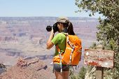 Hiking photographer taking pictures in Grand Canyon at hike by south rim by Bright Angle trail. Youn