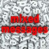 The words Mixed Messages on a background of random letters and words to illustrate poor communication or a bad misunderstanding between people involved in mistaken communication