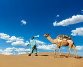 Rajasthan travel background - Indian cameleer (camel driver) with camels in dunes of Thar desert. Jaisalmer, Rajasthan, India
