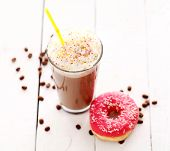 Ice coffee with whipped cream and donut with glaze on a white table