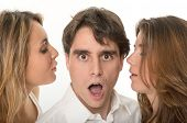Two girls whispering in the ears of a young man with a shocked expression