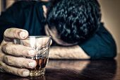 stock photo of hangover  - Depressed drunk man holding a drink and sleeping with his head on the table   - JPG