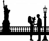 Young man giving his girlfriend a bouquet of flowers in New York silhouette